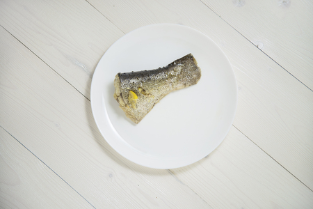 gilt head: Grilled fish on white plate on white wooden background
