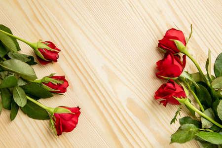 红玫瑰在一张木桌,用花装饰的框架。有一个文字的地方。明信片到恋人那天,3月8日。