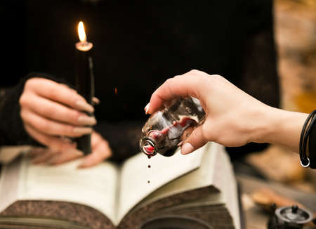 The witch conducts a ritual, drips wine on the witchcraft book