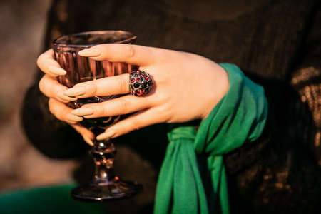 A womans hand with a ring on her finger holds a ritual glass.