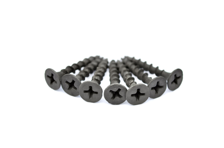 Metal fasteners. Black tapping screws for construction, isolated on a white background, close-up. Selective focus.