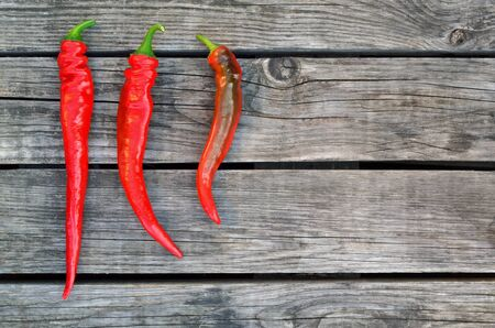 Three red hot chili peppers on an old wooden table as a background. Close-up, top view