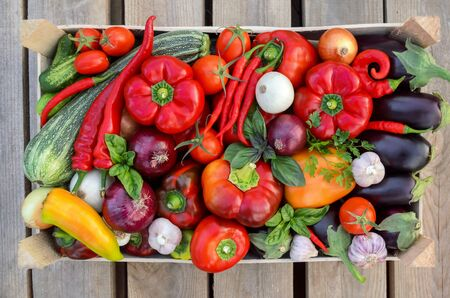 Harvest fresh vegetables in a box on a wooden background, top view. The concept of healthy food.