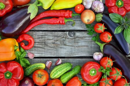 Various fresh vegetables on a rustic wooden background with copy space in the center, top view. The concept of healthy food.
