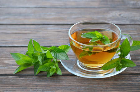 Cup of freshly made hot mint tea with fresh green mint leaves on a old wooden table. Concept of a healthy lifestyle.