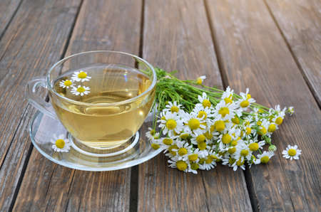 Bouquet of Matricaria chamomilla and cup of chamomile tea on a wooden table close-up. Concept of a healthy lifestyle. Banque d'images