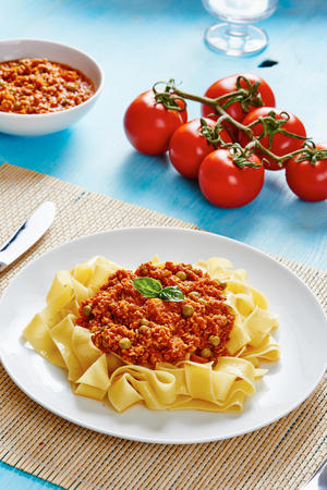bolognese sauce: Tagliatelle with Bolognese sauce on white dish surrounded by ingradients
