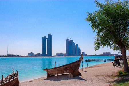Arabic dhow boat on the sandy shore in front of skyscrapers
