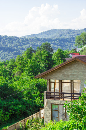 Detached two-storey house with a veranda and a red roof in the forest on the mountain on a clear day