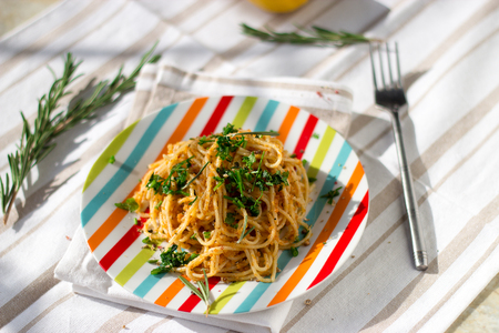 Spaghetti pasta with bread crumbs, lemon and herbs. With a fork, lemon and rosemary in the background