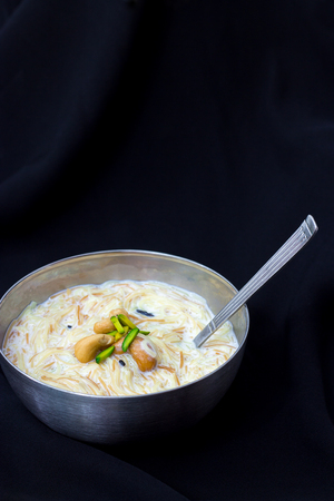 Sweet kheer or khir payasa or sheer khurma Seviyan - famous indian dessert with milk and rice or vermicelli. Vertical. Copy space
