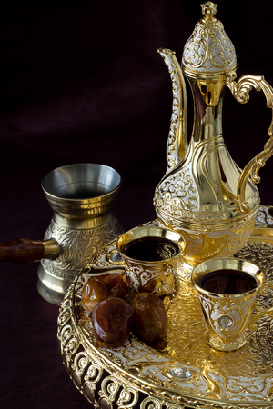 Still life with Traditional golden Arabic coffee set with dallah, coffee pot and dates. Dark background. Vertical photo Stock Photo