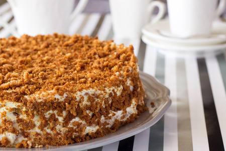 Homemade delicious honey cake with crumb. White tea set on background. Selective focus. Banque d'images