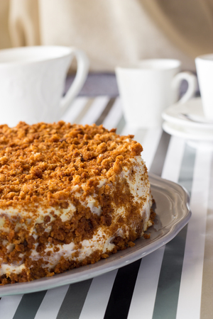 Homemade delicious honey cake with crumb. White tea set on background. Selective focus Stock Photo