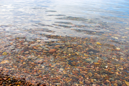 distorted image: Pebbles and small stones on the seabed in a transparent and clean water. Texture, background. Selectiv focus