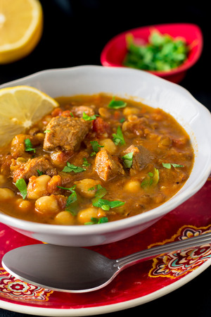 Famous moroccan soup harira with meat, chickpeas, lentils, tomatoes and spices. Dark vertical photo