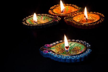 Four burning colorful candles for Diwali celebration on black background.
