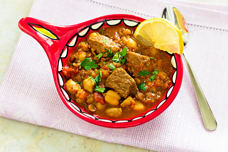 Moroccan soup harira with Meat Chickpeas Lentil Tomato Lemon and Spices in traditional arabic plate. Top view. Copy space