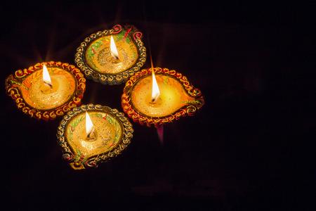 Four burning colorful clay diya lamp Diwali celebration. Black background.