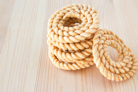 murkoo: Chakli or Murukku popular vegetarian snack South India. Spiral shaped crisp deep-fried snack. Wooden background. Selective focus. Copy space.