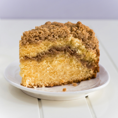 Homemade Cinnamon crumble coffee cake on white wooden background. Square photo. Stock Photo