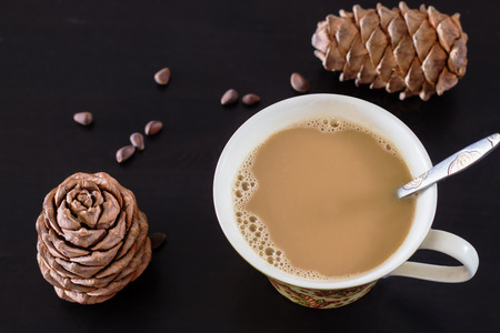 Coffee or milk tea chai with pine nuts cedar vegan milk. Black wooden background and cones of Siberian cedar pine. Top view. Selective focus. Stock Photo
