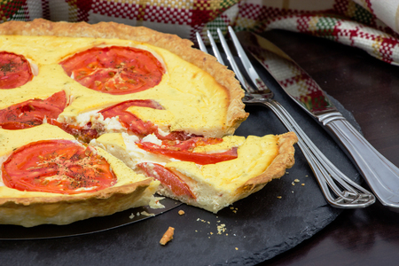 Homemade vegetarian tart with ricotta and organic tomatoes. Black slate background. Close up. Selective focus.
