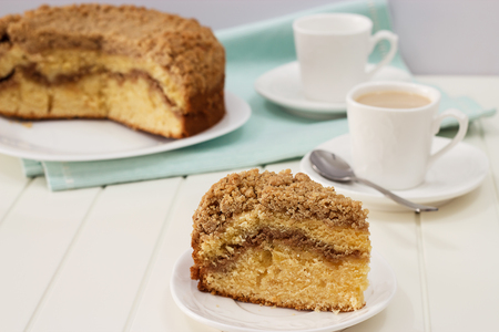 Close up piece of homemade Cinnamon crumble coffee cake and cup of milk tea. White wooden background.