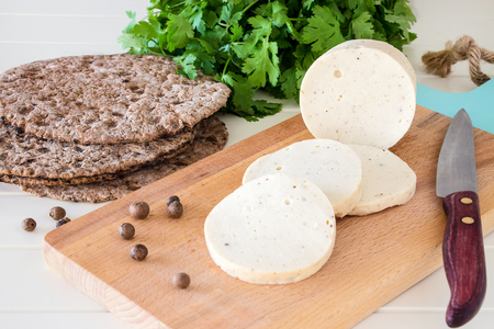 Dietary homemade boiled sausage mortadella from chicken breast with spices on a wooden cutting board. Protein rye multicereal flatbread. White background.