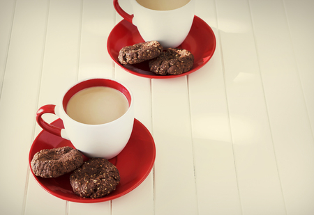 Chocolate oatmeal cookies and cup of milk tea. Valentines day concept. White wooden background. Selective focus. Toned photo. Stock Photo