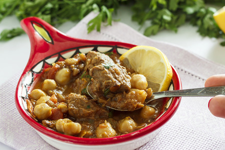 Delicious Moroccan soup harira with meat, chickpeas, lentils, tomatoes and spices. Tradition food for Iftar in holy month of Ramadan.