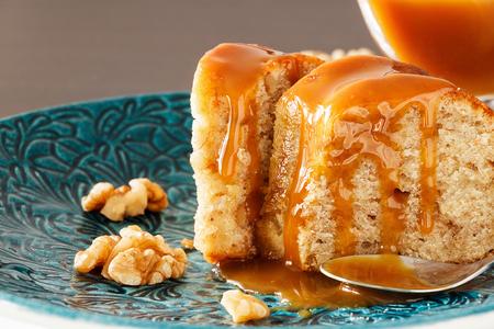 クルミとキャラメルファッジのバナナケーキ。ブループレートの背景。クローズアップ。選択的な焦点。