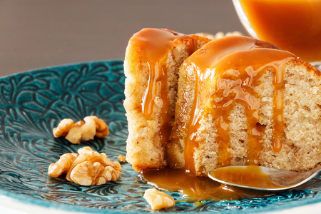 Piece of Banana cake with walnut and caramel fudge. Blue plate background. Close up. Selective focus.