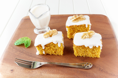 Pieces of homemade carrot cake with icing cream on white plate. Selective focus. Close up.