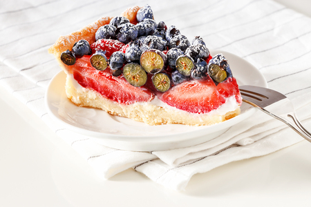 Serving homemade mix berry tart with fresh raspberries, blueberries, strawberries and ricotta cheese cream on white plate. Towel background. Archivio Fotografico