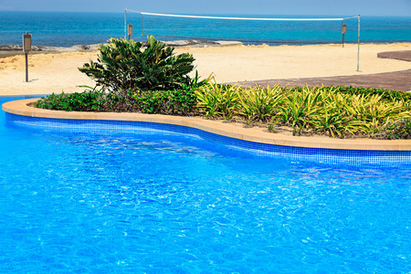 View of the blue water of the pool and sandy beach with a volleyball court. Tropical paradise. Stock Photo
