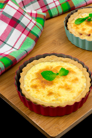 Two homemade quiche with chicken, cheese, cream, onion and mint on wooden background. Above