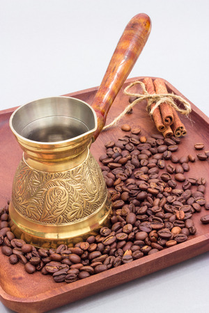 Copper coffee pot or ibrik with coffee beans and cinnamon sticks. On a wooden plate board. White background