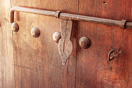 Old wooden door with vintage metal decoration latch. Arabian style. Toned photo. Selective focus.