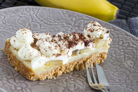 Piece of Banoffee pie with banana, chocolate, caramel and whipped cream. Selective focus.