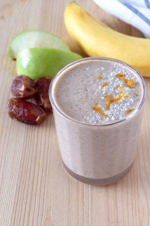 Healthy organic date, banana and apple milk smoothie powdered shredded coconut and orange zest. Fresh diet breakfast. Wooden background. Selective focus.
