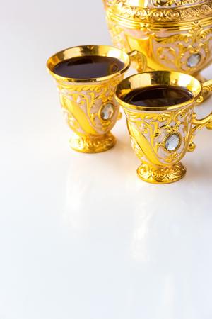 Stillleben mit traditionellem goldenem arabischen Kaffeesatz mit Dallah und Tasse. Weißer Hintergrund. Ramadan-Konzept.