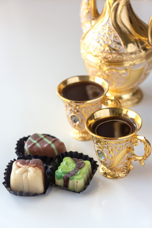 Still life with traditional golden arabic coffee set with dallah, cup and chocolate candy. White background.