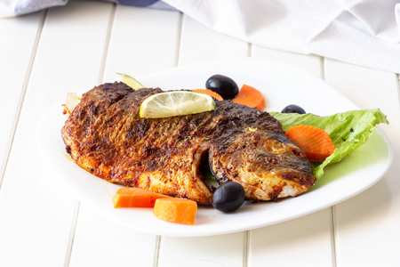 Grilled fish sea bream with vegetables on white plate. White background. Healthy diet food concept. 免版税图像