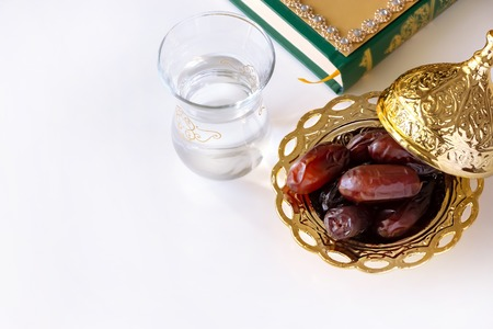 Organic dried dates in traditional arabic golden plate, cup of pure drinking water and quran book. Ramadan concept.