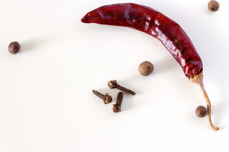 Dry red chilli long Kashmiri pepper, Cloves and Allspice isolated on white background. Close up. Copy space. Top view.