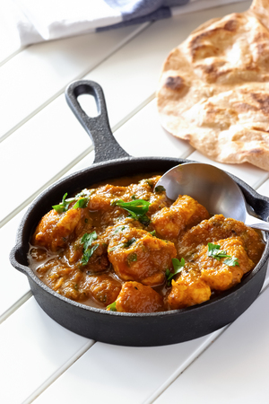 Close up traditional Indian butter chicken curry and lemon served with chapati bread on iron-cast. White wooden background.