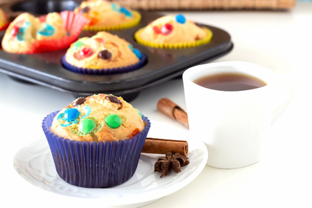 Homemade lemon muffins with colorful chocolate candy in paper case and cup tea. White background. Selective focus.