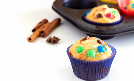 Homemade lemon muffins with colorful chocolate candy in paper case. White background. Selective focus