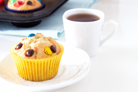 Homemade lemon muffins with colorful chocolate candy in paper case and cup of tea. White background. Selective focus Stock Photo